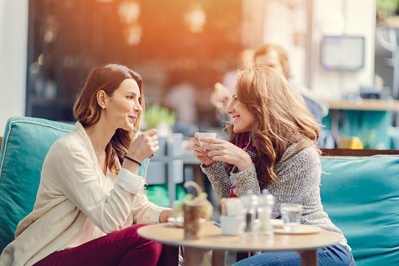 mujeres sentadas en la terraza de una cafetería